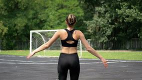 Back view on Young Athlete Woman in Sport Outfit Engaged in Fitness on the Sports Field in the Park. stock footage