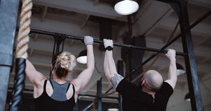 Back view young athletic Caucasian man and woman working out doing pull-ups slow motion. Healthy lifestyle concept. Back view young athletic Caucasian man and stock video footage