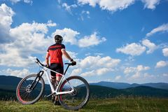 Back view of young athletic professional tourist biker standing at bike on top of hill stock photography