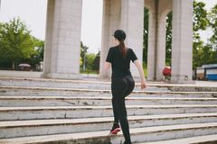 Back view of young athletic strong brunette girl in black uniform and cap doing sport exercises, warm-up before running stock images
