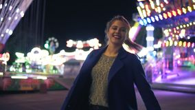Back view of young attractive girl with ponytail walking forward then turning around smiling and looking at camera. Hanging out in amusement park with stock video
