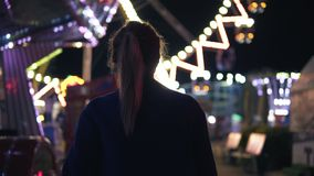 Back view of young attractive girl walking forward then turning around smiling and looking at camera hanging out in. Amusement park with attractions background stock footage