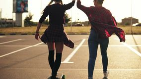 Back view of young attractive hipster girl being taught skateboarding by a friend who is supporting her holding her hand. Slowmotion shot. Lens flare. Camera stock footage