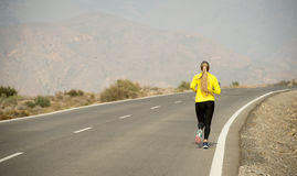 Back view of young attractive sport woman running on desert mountain asphalt road stock photography