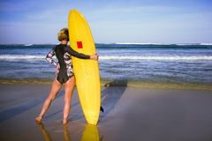Back view of young attractive and sporty surfer girl in cool swimsuit at the beach holding yellow surf board looking at the blue s stock image