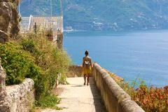 Back view young backpacker woman walking the path that runs along Amalfi Coast, Italy stock images