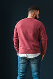Back view. A young bearded handsome male hipster, dressed in a red pullover with long sleeves and jeans, stands indoors. Stock Image