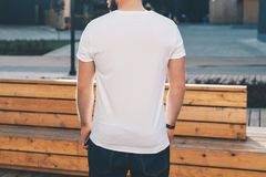 Back view. Young bearded hipster man dressed in white t-shirt and sunglasses is stands on city street. Mock up. Stock Image