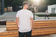 Back view. Young bearded hipster man dressed in white t-shirt and sunglasses is stands on city street. Mock up. Stock Photography