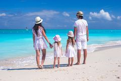 Back view of a young beautiful family on tropical beach Royalty Free Stock Photo