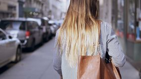 Back view of young beautiful woman with bag walking in the city centre of New York, America, exploring city.