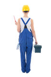 Back view of young beautiful woman builder in workwear with tool Stock Image