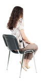 Back view of young beautiful  woman sitting on chair. Stock Images