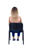 Back view of young beautiful  woman sitting on chair. Royalty Free Stock Photography
