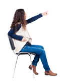 Back view of young beautiful  woman sitting on chair and pointin Royalty Free Stock Photo