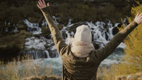 Back view of young beautiful woman standing near the waterfall and raising hands up, feeling freedom and happy. Traveling woman enjoying the beautiful view of stock video footage