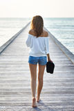 Back view of young beautiful woman walking on the pier Royalty Free Stock Photo