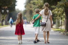 Back view of young blond long-haired woman walking with two children, small daughter and son along sunny park alley on blurred stock photos