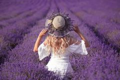 Back view of Young blond woman in lavender field. Happy carefree. Female in a white dress and straw hat enjoying sunset. Outdoors portrait royalty free stock photo