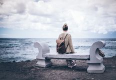 Back view of young woman in long dress and with backpack sitting on stone bench by sea royalty free stock photo
