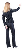 Back view of young blonde business woman pointing at wal Stock Photo