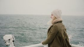 Back view of young blonde woman standing on the ship and looking wistfully on the sea, exploring the Iceland. Tourist female traveling on the boat alone stock video