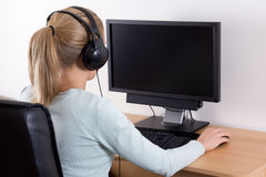 Back view of young blondie woman using a computer and listening Stock Images