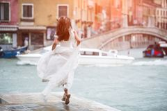 Back View of young bride running to lake. Italy, Venice royalty free stock image