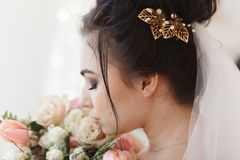Back view of young brunette bride with barrette in hair. Flower bouquet on background. Close-up facial portrait.  stock photo