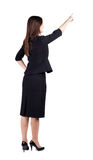 Back view of young brunette business woman pointing at wall. Royalty Free Stock Photo