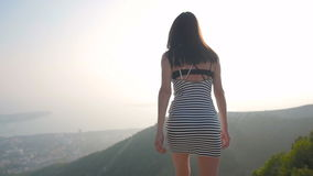Back View of Young Brunette Go To The Edge of The Mountains And Stretching Arms stock footage
