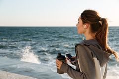 Back view of young brunette sport woman holding bottle of water. While listening to music, seaside outdoor Royalty Free Stock Photos