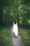 Woman in a white dress walking through a forest. Back view of a young brunette woman, dressed in an elegant white dress, walking on a pathway through spring Stock Photos