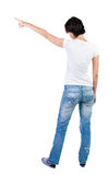 Back view of young brunette woman pointing at wall. beautiful gi Stock Photo