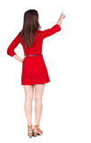 Back view of young brunette woman pointing at wall. Stock Photography