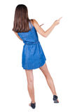 Back view of young brunette woman pointing at wall. cheerful gir Royalty Free Stock Photo
