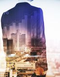 Finance concept. Back view of young businessman on abstract city background with business chart. Finance concept. Double exposure Royalty Free Stock Image
