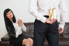 Back view of young businessman hiding gift box for Stock Image
