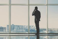 Back view of young businessman is looking out of a panoramic window and talking by phone stock photo