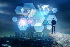 Artificial intelligence and mind concept. Back view of young businessman on mountain top looking at abstract circuit brain interface on blurry illuminated night royalty free stock photos