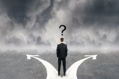 Different direction and confusion concept. Back view of young businessman with question mark and two arrows on concrete road. Cloudy sky background. Different stock images