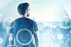 Research, technology and finance concept. Back view of young businessman on rooftop with digital business interface. Research, technology and finance concept stock photo