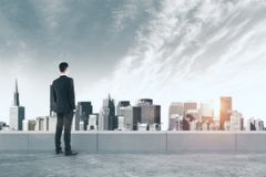Employment concept. Back view of young businessman on rooftop looking into the distance on city background with sunlight. Employment concept Stock Photography