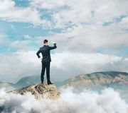 Employment concept. Back view of young businessman standing on mountain top and looking into the distance. Employment concept Royalty Free Stock Images