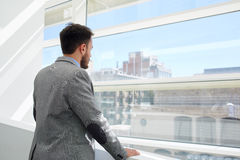 Back view of a young businessman thinking about something while looking in big office window Stock Photo