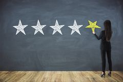 Rating and appraisal concept. Back view of young businesswoman drawing stars on chalkboard wall. Rating and appraisal concept royalty free stock images