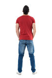 Back view of young casual man with hands in pockets looking up. Full body length portrait isolated over white studio background Stock Images
