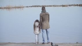 Back view of young Caucasian father standing with daughter on riverbank and talking. Wide shot of man and little girl