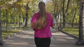 Back view of a young Caucasian girl with long tail hair wearing sportswear running in the autumn park. Female runner. Portrait of smiling Caucasian woman in pink stock video footage