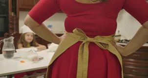 Back view of young Caucasian woman in red dress tying bow on apron and putting hands on hips. Little girl sitting at the stock footage